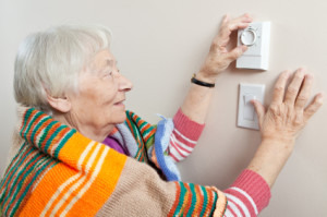 Woman turning up thermostat